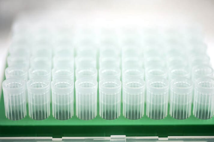 Clear plastic test tubes in green holders