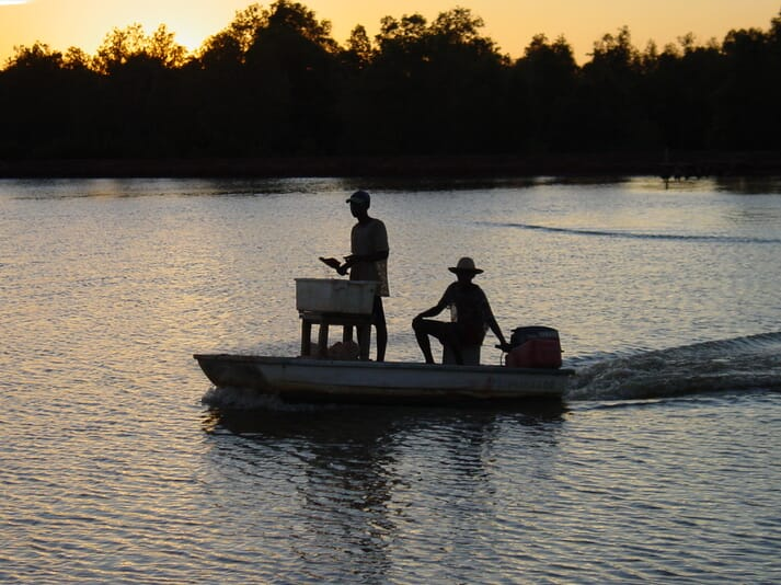Two people driving a boat across a pond