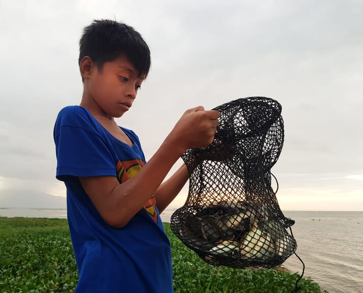 A boy with local fish species in the Philippines