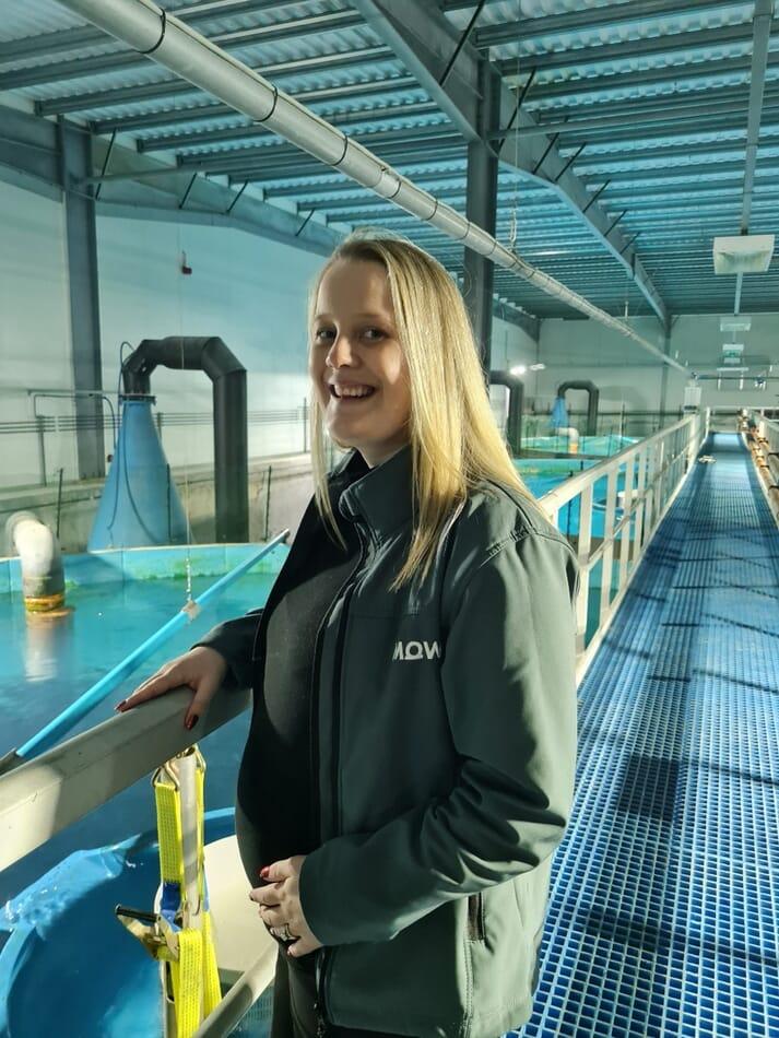 Woman standing near a series of indoor recirculating tanks