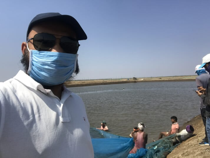 Man wearing a surgical mask at the edge of a shrimp pond