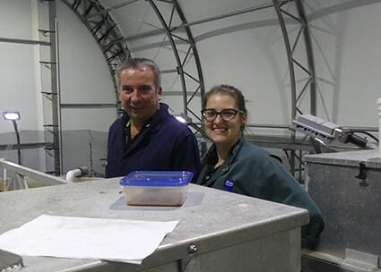 Two fish farmers standing in an indoor smolt production facility