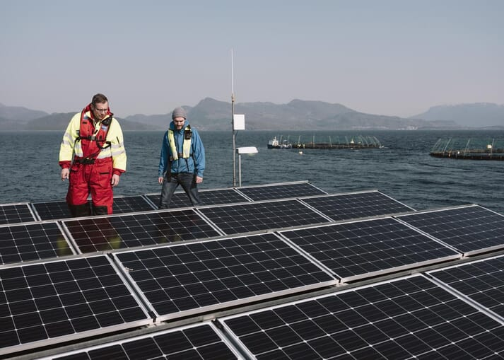 Kjetil Ørnes (Grieg Seafood Rogaland production manager) (left) and Helleik Syse (right) with the solar panel array on top of the feed barge