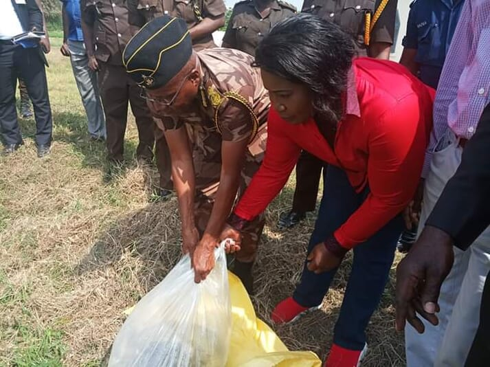 Elizabeth Afoley Quaye and a prison officer stocking tilapia fingerlings into the prison pond