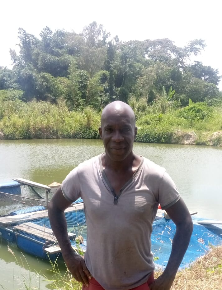 man standing in front of a fish pond