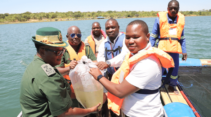 Zimbabwe Prison and Correctional Service (ZPCS) officer commanding Matabeleland North Province Senior Assistant Commissioner Moddie Nkomo (left) helps ZPCS Commissioner-General Paradzai Zimondi (in glasses) to commission the ZPCS fish farming project at Bubi-Lupane Dam