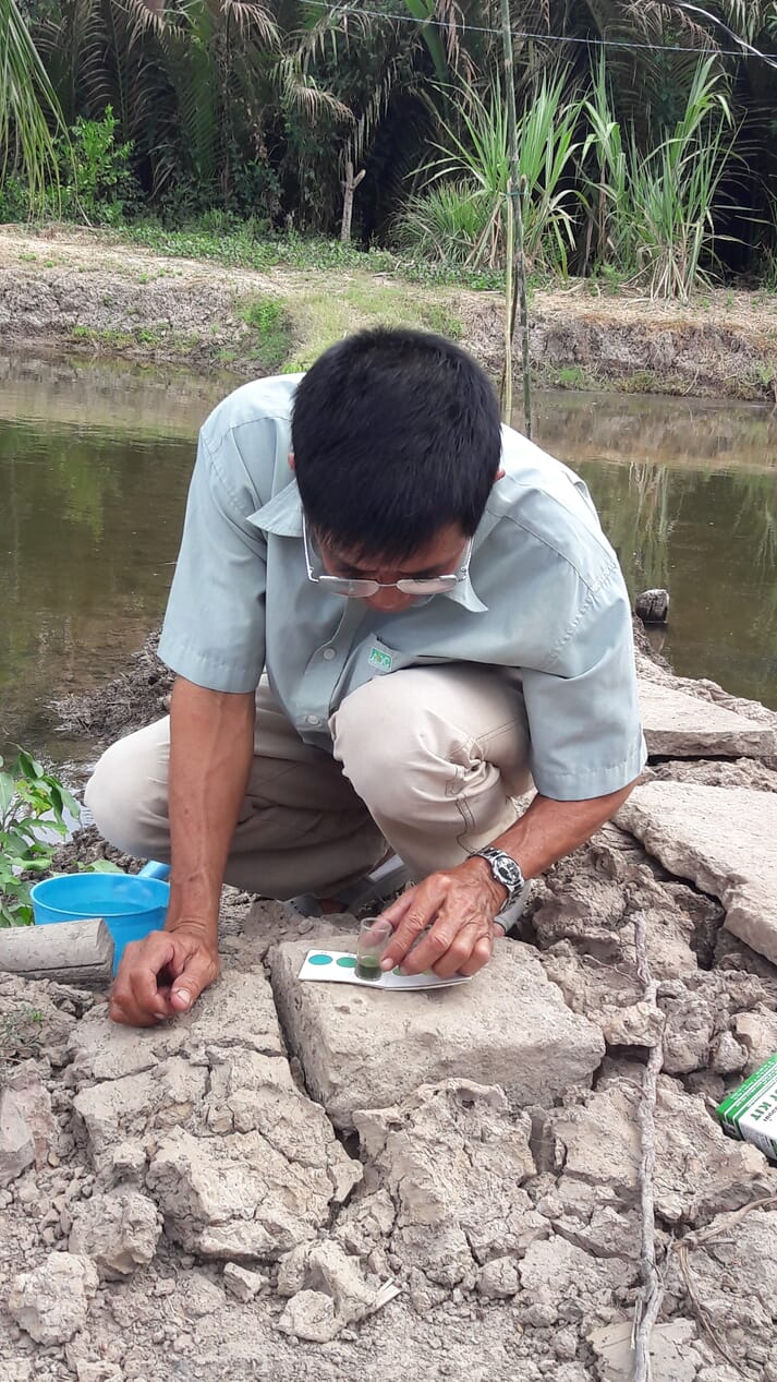 Person conducting a water quality test at the edge of a fish pond