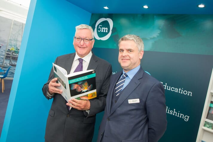 Fergus Ewing, Scotland's Cabinet Secretary for Rural Affairs, with Matt Colvan of 5m Publishing dip into Jim Treasurer's new book at Aquaculture UK