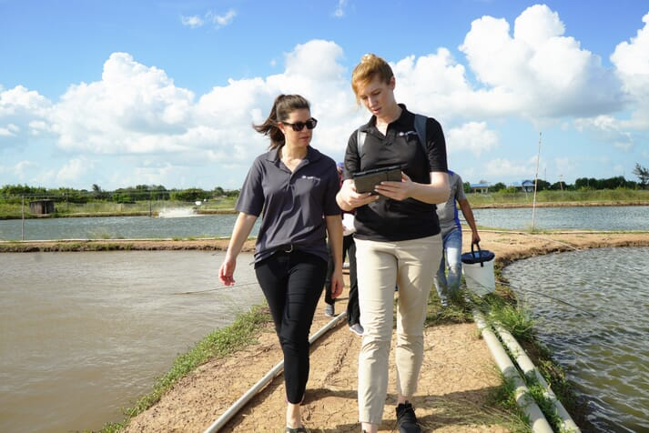 Valerie Robitaille and Chelsea Andrews visiting a shrimp farm in Asia