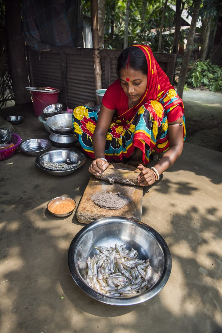 Shantona Rani smashing mola, to be mixed with lentils and sweet potato for her family's lunch at Madhob Pasha, Bangladesh