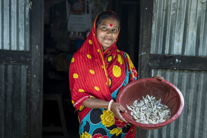 Shantona Rani showing the mola fish she harvested using a gill net from her pond in Madhob Pasha, Bangladesh