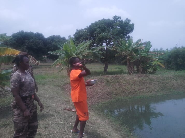 Inmate working at the tilapia pond